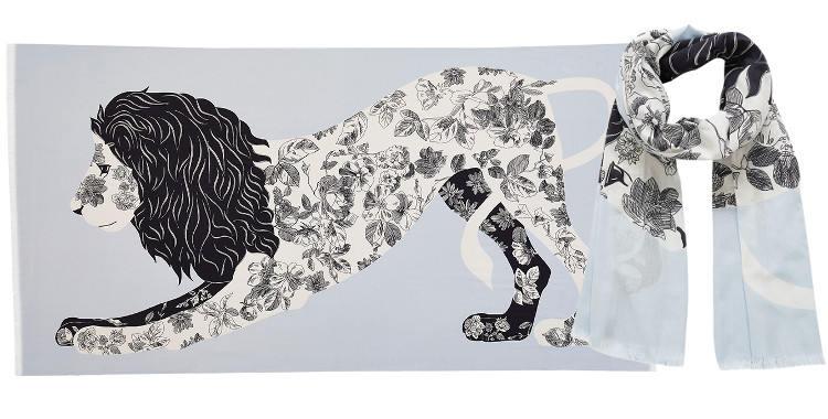 Ce foulard imprimé en coton, représente un lion majestueux au corps tatoué d'un motif foral, en coloris bleu ciel.