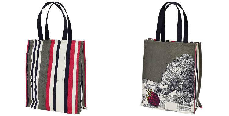 Ce sac Inouitoosh, en coton canvas imprimé, représente un lion et une framboise sur un sol en damiers noirs et blancs.
