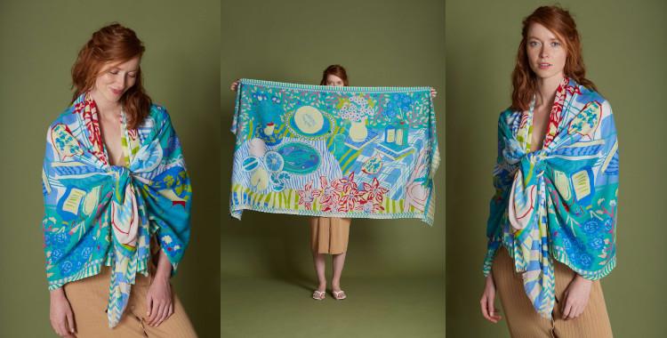 Ce foulard paréo, Inouitoosh, été 2021, représente une table de vacances dressée avec des fruits de mer, des fleurs et des fruits de saison, en vert
