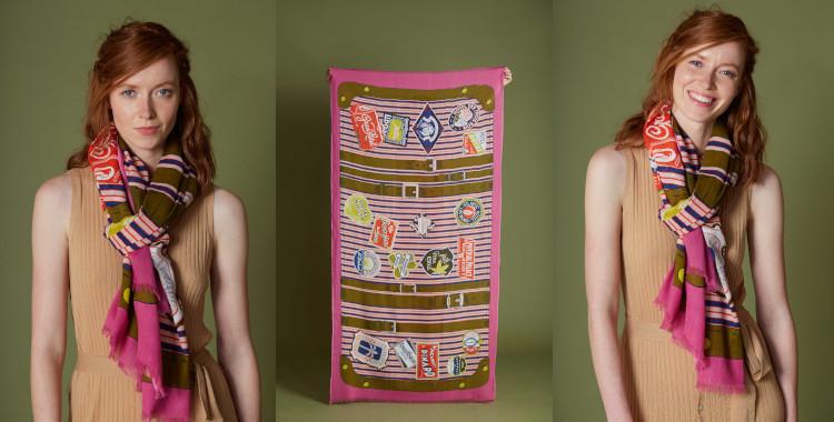 Ce foulard, rose, Inouitoosh été 2021, a pour motif une valise avec ses tampons et écussons des pays, régions et villes du monde entier.